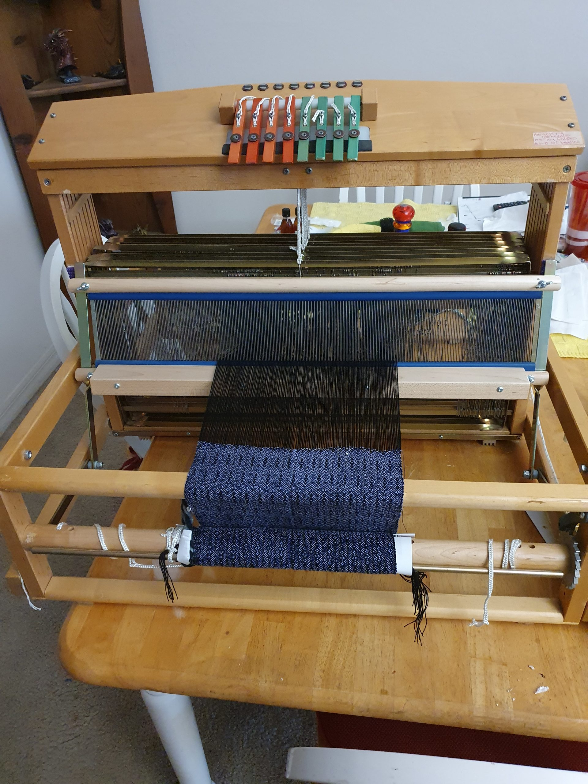 A weaving loom sitting on a dining table. There's a purple and black scarf project on it.
